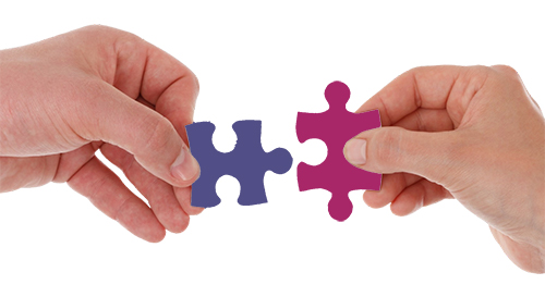 Hands connecting puzzle pieces